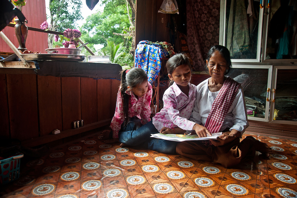 """Chheu Teal Korng village:.Remarkable how much CWS has accomplished here in less than a.year, because they are working with such a willing and committed local committee. Kindergarten for 21 students in village.  Teacher is 18 year old Nen Sras who said, """"These children grow up so far from everything.  With this.Kindergarten I can at least give them a headstart for primary.school."""" Many of the adults in this community are illiterate, and have a.strong desire that their kids get an education.  Indoor shot of granddaughter reading to her Grandma is Chhorn Leakhana (10) reading to Grandma Chhay Train (52).  With her is cousin Moeun Siev May (11)."""