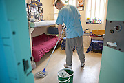 An enhanced prisoner cleaning his cell floor on H wing at YOI Aylesbury.