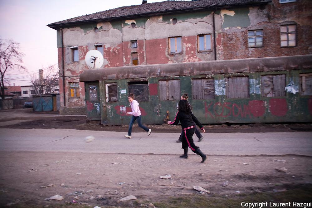 24022008. Près de la gare de Fushe Kosovo. Des enfants albanais jouent au football entre les rails et les habitations. Derrière eux, un wagon qui sert de logement et un immeuble d'habitation qui est une ancienne prison. Ce quartier était à majorité serbe avant la guerre.