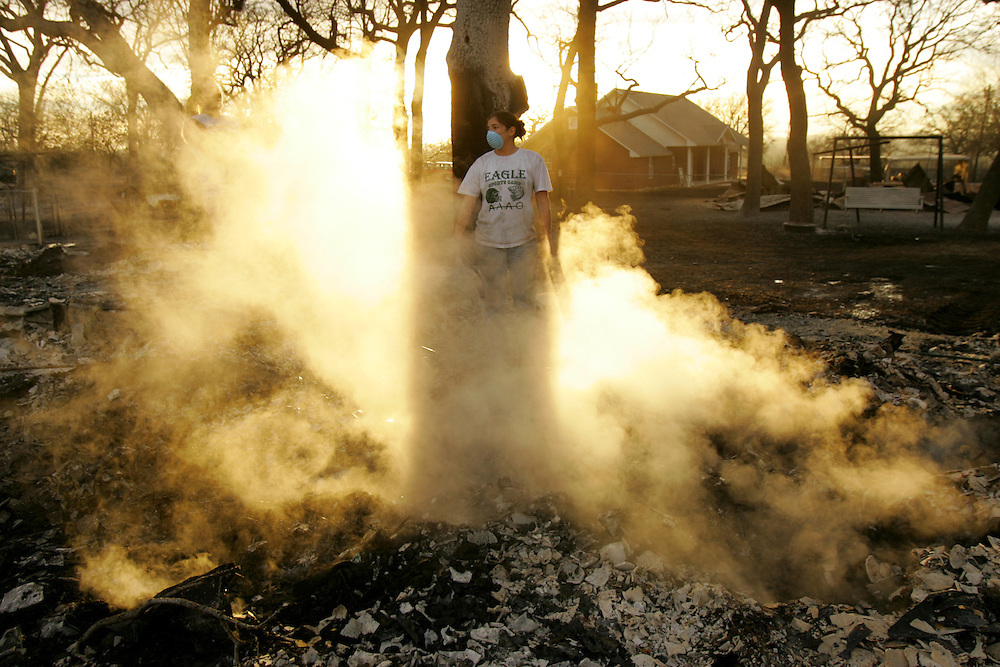 © 2005 Alex Jones www.alexjonesphoto.com..Roni Richards cools of burning debris at the site of her grandmother-in-law's home on Wednesday, December 28, 2005 in Cross Plains, Texas.  The town was heavily damaged by an uncontrolled grass fire on Tuesday, one of many in the state.