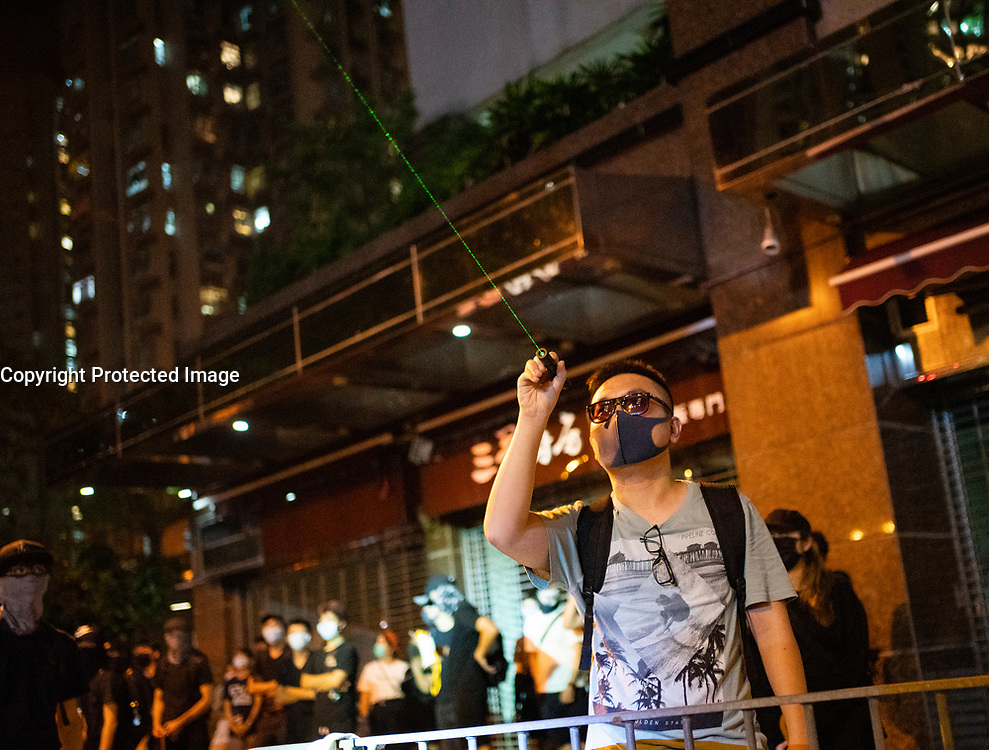 Hong Kong, China. 9th October 2019. Large peaceful crowd gathered to sing songs at MOStown mall in Ma On Shan in solidarity with several security guards who were arrested by police this week. Later small group of protestors went to nearby Shatin Divisional Police Station and shouted abuse at the police and threw objects. Riot police later charged but no arrests made. Protestor shines laser pen towards police. Iain Masterton/Alamy Live News.