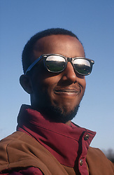 Portrait of young man wearing sunglasses smiling,