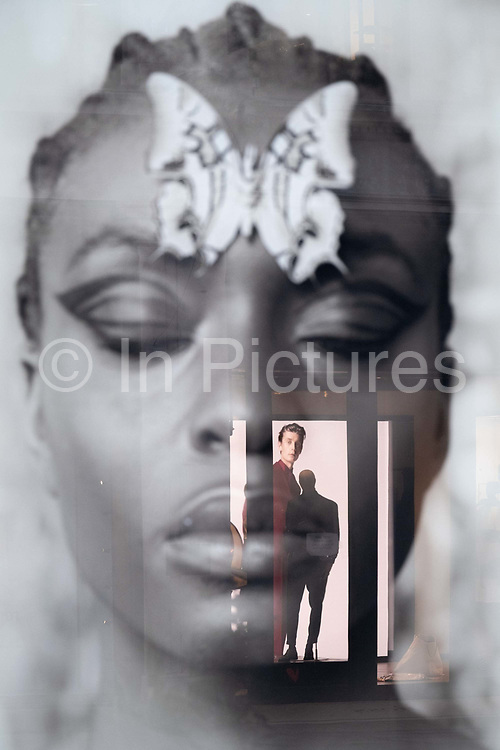 A male mannequin stands alongside a model occupying a reflected aperture within a womans face, in a retail window space on Regent Street on 5th February 2021, in London, England.