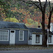 Autumn in Arrowtown. Historic Cottages at the end of town. Arrowtown is the much visited, historic, 4-season, southern hemisphere holiday destination, located only 20 minutes drive from Queenstown, South Island, New Zealand. Arrowtown is a former gold-mining town built on the banks of the Arrow River, once a rich source of gold in the 1860's and now a sophisticated, multi-cultural town catering visitors from around the globe. Arrowtown offers an ambiance with its shops, restaurants, cafes, offices and galleries located within a tight precinct. Photo Tim Clayton