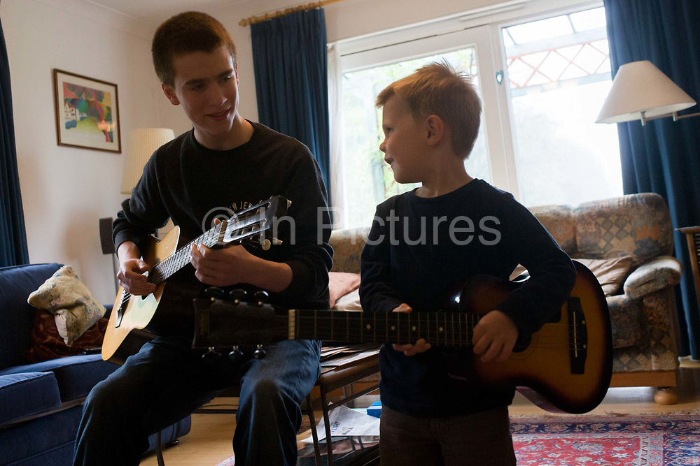 A 16 year-old teenager and his 4 year-old cousin smile at each other while playing acoustic guitar together in the family living room. Playing their musical instruments, the older boy knows how to pluck the strings to make a pleasant sound while the younger lad simply brushes his fingers across the strings to make a noise. But music brings their age gap closer as they perform a pretend concert in front of family elders.
