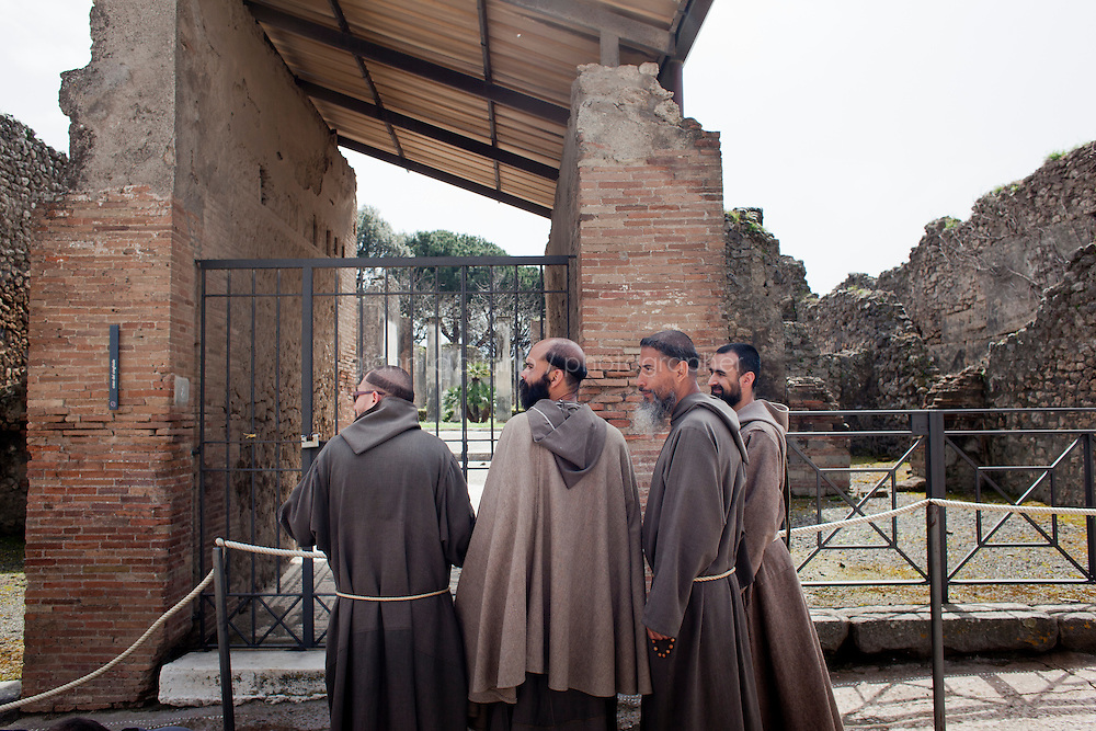 POMPEII, ITALY - 4 APRIL 2013: Franciscan monks walk on Via dell'Abbondanza (Abundance street) in Pompeii, Italy, on April 4th, 2013...In recent years, a series of collapses at the site have alarmed conservationists, who warn that the ancient Roman city is dangerously exposed to the elements ? and poorly served by the red tape, lack of strategic planning and limited personnel of the site's historically troubled management. ..Pompeii, along with Herculaneum, was buried under 4 to 6 meters (13 to 20 ft) of ash and pumice in the eruption of Mount Vesuvius in 79 AD. After its initial discovery in 1599, Pompeii was rediscovered as the result of intentional excavations in 1748 by the Spanish military engineer Rocque Joaquin de Alcubierre...Pompeii is an UNESCO World Heritage Site and one of the most popular tourist attractions of Italy, with approximately 2.5 million visitors every year...Gianni Cipriano for The New York Times