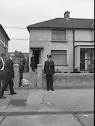 """John O'Grady Rescued By Gardai.   (R67)..1987..05.11.1987..11.05.1987..5th November 1987..After being kidnapped from his home in Cabinteely, Co Dublin, John O'Grady was finally rescued after twenty one days in captivity. he was located in a house inCarnlough Road, Cabra West, Dublin. During his ordeal Mr O""""Grady was mutilated by the kidnappers led by Dessie O'Hare to apply pressure on his family to pay the ransom sought. In an ensuing gun battle with the kidnappers a detective garda was shot and seriously wounded. In the chaos that followed the kidnappers escaped and were not all captured for a further three weeks after a massive manhunt...Image shows senior Gardai arriving at the scene of the rescue of John O'Grady. A bouquet was laid at the gate by a wellwisher."""