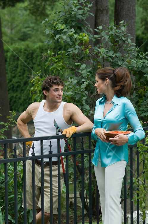 woman talking with her gardener by a fence