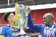 AFC Wimbledon striker Lyle Taylor (33) and AFC Wimbledon striker Adebayo Akinfenwa (10) with the trophy. AFC Wimbledon promotion to League One, after beating Plymouth Argyle Football Club 2-0 during the Sky Bet League 2 play off final match between AFC Wimbledon and Plymouth Argyle at Wembley Stadium, London, England on 30 May 2016. Photo by Stuart Butcher.