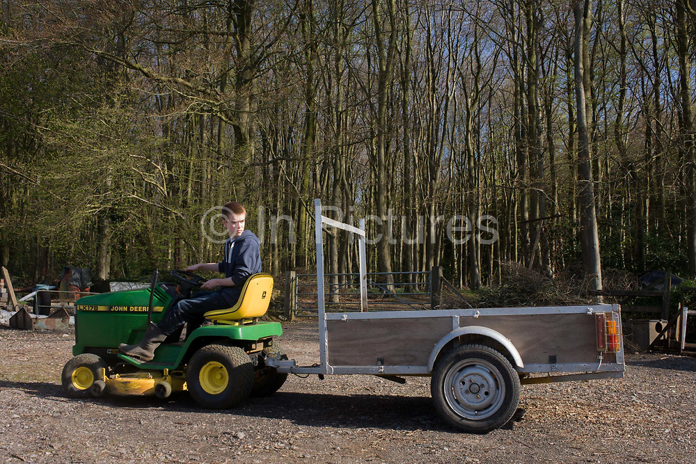 A teenage boy of 15 years of age learns the art of reversing a small trailer on a family farmstead in north Somerset. While steering the small garden mower, he looks behind him to guage the way the front wheels turn against the rear - gaining experience of how opposite locks on their turning circles change the path of two interlinked vehicles. In the background are tall beech trees set in a small wood on the small farm. The yard has a smooth ground gravel and stone on which to practice driving.