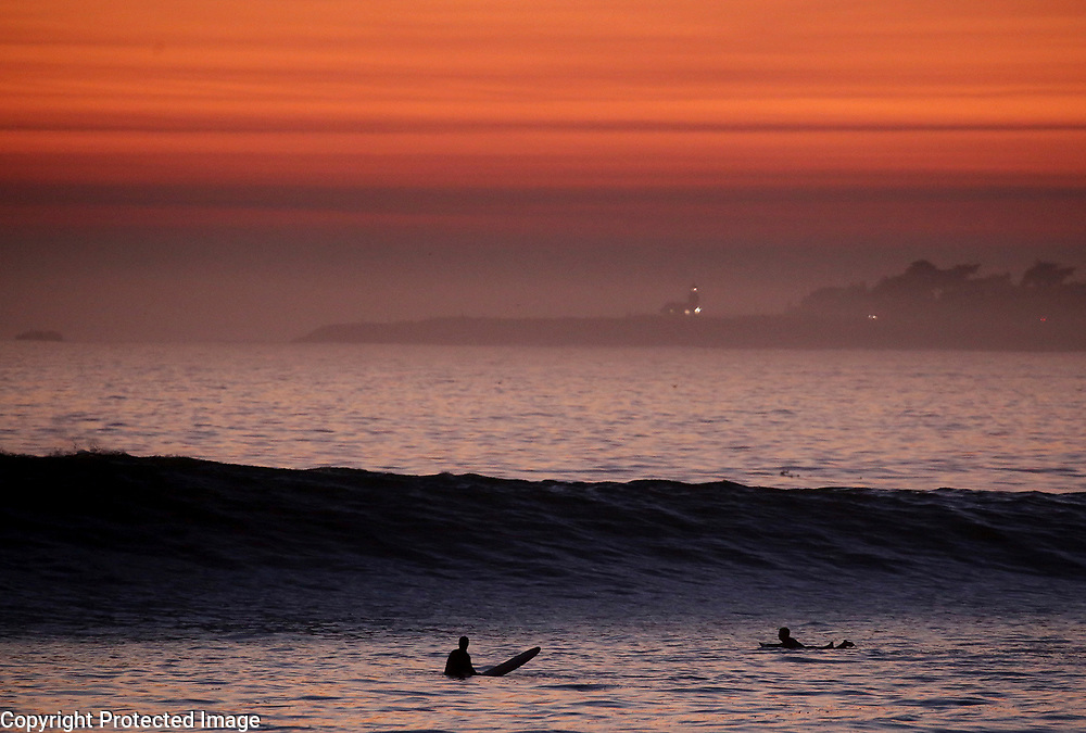 Two surfers work to get in a last ride as a large swell pours in to Moran Lake Beach near Pleasure Point in Santa Cruz, California as the sunset paints the sky a fiery orange above Lighthouse Point in the distance.<br /> Photo by Shmuel Thaler <br /> shmuel_thaler@yahoo.com www.shmuelthaler.com