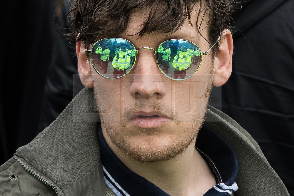 "© Licensed to London News Pictures. 11/03/2018. London, UK. An alt right protesters looks at rows of police , reflected in his sunglasses . Alt right group Generation Identity and other far-right groups hold a demonstration at Speakers' Corner in Hyde Park , opposed by antifascists . Generation Identity supporters Martin Sellner and Brittany Pettibone were due to speak at the demo but were arrested and detained by police when they arrived in the UK , also forcing them to cancel an appearance at a UKIP "" Young Independence "" youth event , which in turn was reportedly cancelled amid security concerns . Photo credit: Joel Goodman/LNP"