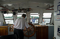 Captain Bob Reed navigates the MV Sophie C through the islands on Lake Winnipesaukee during her afternoon mail delivery cruise.  (Karen Bobotas/for the Laconia Daily Sun)