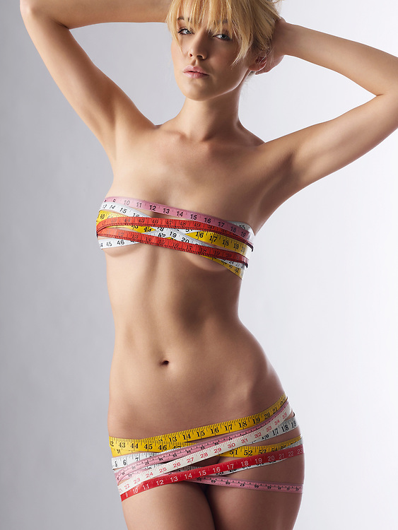 Slender blond nude woman with multiple measuring tapes wrapped around her breasts and hips