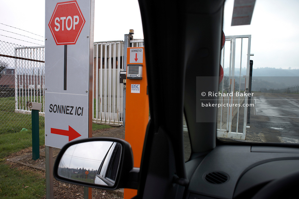 Opening security gate asking visitors to stop and ring here at the Delacre biscuit production factory in Lambermont, Belgium.