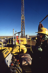 Stock photo of a man operating machinery at a fracking work site