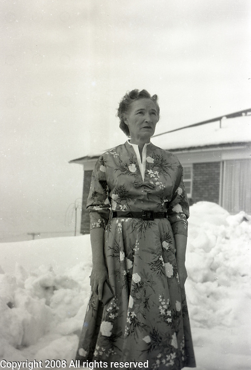 An elderly woman stands outside in the snow wearing a spring or summer dress.