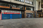 Closed tourist shop and The Invisible Man poster in front of a boarded up cinema in Leicester Square in the centre of Londons cinema land, empty during the coronavirus pandemic on the 10th May 2020 in London, United Kingdom. The main headline What you cant see can hurt you has a savage irony during the COVID lockdown.