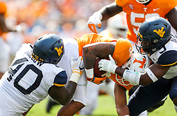 Sep 1, 2018; Charlotte, NC, USA; West Virginia Mountaineers defensive lineman Kenny Bigelow Jr. (40) and West Virginia Mountaineers safety Toyous Avery (3) tackles Tennessee Volunteers running back Tim Jordan (9) during the first quarter at Bank of America Stadium. Mandatory Credit: Ben Queen-USA TODAY Sports