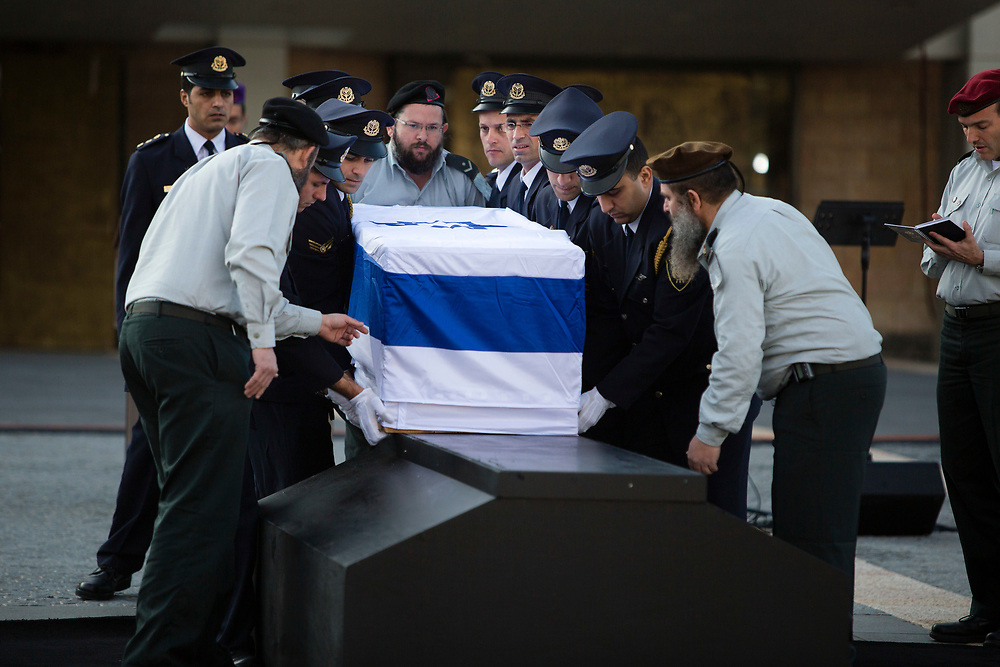 Members of the Knesset honor guard carry the flag draped coffin of former Israeli Prime Minister Ariel Sharon, prior to a state memorial ceremony at the Knesset, Israel's parliament in Jerusalem, on January 13, 2014. Sharon, a former Israeli general and prime minister, died Saturday, aged 85, after eight years in a coma caused by a stroke.