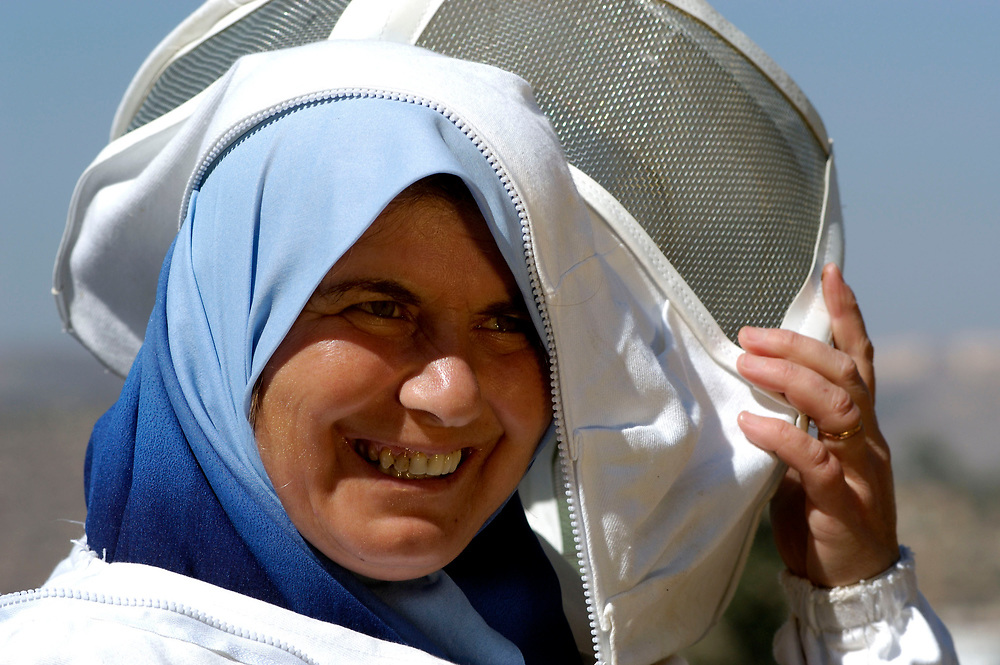 Khitam Jaghoub takes off her beeekeeping suit. The Palestinian woman participates in an income generating program carried out by International Orthodox Christian Charities in the West Bank village of Beita.