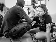 """14 MARCH 2014 - NAKHON CHAI SI, NAKHON PATHOM, THAILAND: A woman gets a sak yant tattoo at Wat Bang Phra. Wat Bang Phra is the best known """"Sak Yant"""" tattoo temple in Thailand. It's located in Nakhon Pathom province, about 40 miles from Bangkok. The tattoos are given with hollow stainless steel needles and are thought to possess magical powers of protection. The tattoos, which are given by Buddhist monks, are popular with soldiers, policeman and gangsters, people who generally live in harm's way. The tattoo must be activated to remain powerful and the annual Wai Khru Ceremony (tattoo festival) at the temple draws thousands of devotees who come to the temple to activate or renew the tattoos. People go into trance like states and then assume the personality of their tattoo, so people with tiger tattoos assume the personality of a tiger, people with monkey tattoos take on the personality of a monkey and so on. In recent years the tattoo festival has become popular with tourists who make the trip to Nakorn Pathom province to see a side of """"exotic"""" Thailand.   PHOTO BY JACK KURTZ"""