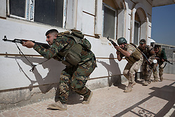 © Licensed to London News Pictures. 09/03/2015. Erbil, Iraq. Kurdish peshmerga fighters keep low as they approach a building entrance during an urban warfare training session run by German soldiers at a partially finished housing estate near Erbil, Iraq. <br /> <br /> The training is part of a four week platoon level infantry training package run by coalition forces aimed at improving the efficiency of the Iraqi Security Forces. Photo credit: Matt Cetti-Roberts/LNP
