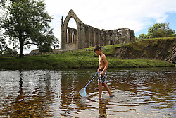 © Licensed to London News Pictures. 06/09/2016. Skipton, UK. 9-year-old Zaid Patel fishes in the River Wharfe as the sun shines and temperatures rise at Bolton Abbey near Skipton in North Yorkshire. Forecasters are predicting the hottest start to Autumn since the 1940s as warm air blows up from the south this week. Photo credit : Ian Hinchliffe/LNP