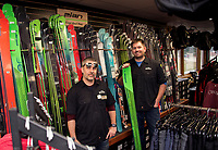 """Jeremy Stottler and Ben Jensen stocking the """"ski wall"""" at the newly renovated Gunstock Ski and Sport Shop.  (Karen Bobotas/for the Laconia Daily Sun)"""