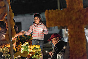 A family lights candles around the gravesite of a family member during the Day of the Dead festival October 31, 2017 in Tzintzuntzan, Michoacan, Mexico.