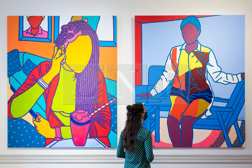 """© Licensed to London News Pictures. 08/10/2020. LONDON, UK. A staff member views """"Sweet Things"""", 2020, and """"Mme. Limbong"""", 2020, both by Ajarb Bernard Ategwa.  Preview of 1-54 Contemporary African Art Fair, the leading international art fair dedicated to contemporary art from Africa and its diaspora, taking place at Somerset House.  The fair showcases the work of more than 110 emerging and established artists from Africa and is the only physical art fair taking place during Frieze Week.  Photo credit: Stephen Chung/LNP"""