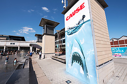 "© Licensed to London News Pictures. 23/08/2019. Bristol, UK. Mural titled ""Cause"" by Bristol artist Jody Thomas which references the instantly recognisable poster from the film ""Jaws"" and aims to highlight the impact of single-use plastic pollution on the Earth's oceans. The piece is painted on a ventilation tower for the underground carpark in Bristol's Millennium Square in collaboration with We The Curious science and arts centre in Bristol's Millennium Square. We The Curious declared their own climate emergency earlier this year, becoming the first science centre in the world to do so. The science centre formed a partnership with Bristol City Council and the University of Bristol, who collectively released a public declaration to become carbon neutral by 2030. Jody who began painting in 1988 also painted the giant mural of Greta Thunberg on Bedminster's Tobacco Factory earlier this yearPhoto credit: Simon Chapman/LNP."