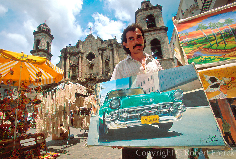 CUBA, HAVANA (HABANA VIEJA) Crafts market in Plaza de la Catedral, artist holding a painting of '57 Chevy, in a city of antique cars