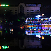 The northwestern shore of Hoan Kiem Lake at night, with lights reflection on the calm water.