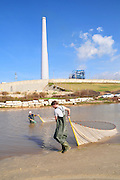 Israel, Hadera, Fishing at the outlet of the Hadera River the coal operated power plant's flues in the background