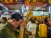 15 OCTOBER 2015 - BANGKOK, THAILAND:  A man prays during the Vegetarian Festival at the Joe Sue Kung Shrine in the Talat Noi neighborhood of Bangkok. The Vegetarian Festival is celebrated throughout Thailand. It is the Thai version of the The Nine Emperor Gods Festival, a nine-day Taoist celebration beginning on the eve of 9th lunar month of the Chinese calendar. During a period of nine days, those who are participating in the festival dress all in white and abstain from eating meat, poultry, seafood, and dairy products. Vendors and proprietors of restaurants indicate that vegetarian food is for sale by putting a yellow flag out with Thai characters for meatless written on it in red.   PHOTO BY JACK KURTZ