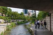 Seoul, South Korea - September 25, 2019: People walk beside the Cheonggyecheon River, an 11 km long revitalized stream that runs through downtown Seoul.