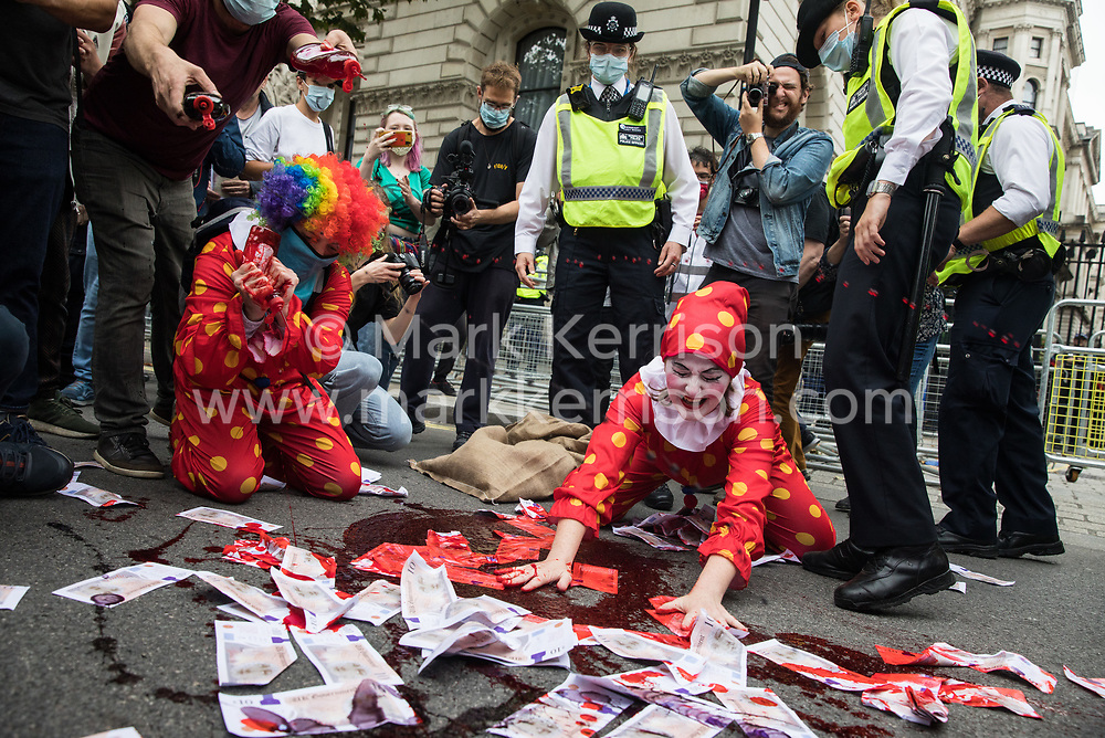 Two clowns spread fake blood and banknotes in the road in front of Downing Street during a 'Carnival of Corruption' protest by climate activists from Extinction Rebellion against the government's facilitation and funding of the fossil fuel industry on 3 September 2020 in London, United Kingdom. Extinction Rebellion activists are attending a series of September Rebellion protests around the UK to call on politicians to back the Climate and Ecological Emergency Bill (CEE Bill) which requires, among other measures, a serious plan to deal with the UK's share of emissions and to halt critical rises in global temperatures and for ordinary people to be involved in future environmental planning by means of a Citizens' Assembly.