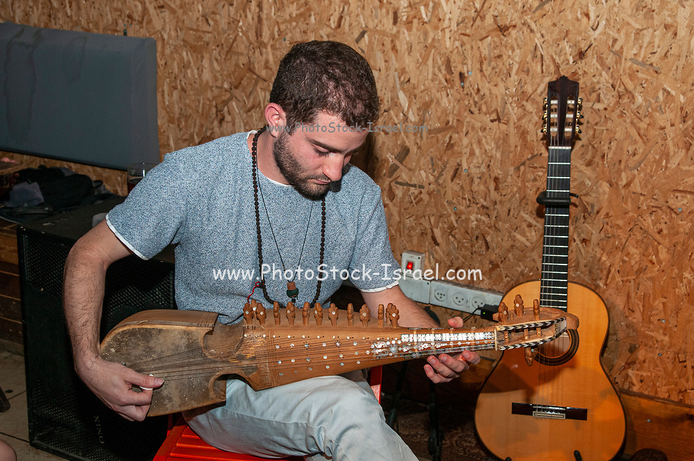 Young Caucasian musician plays an Afghan Rebab bowed string instrument