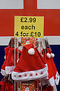 In the week before Chrsitmas, santa hats on sale outside a tourist trinket shop in London's West End. Each one can be bought for £2.99 or 4 for ten pounds. The colours of a Union jack flag is seen in the background.