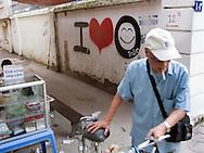 Color film photograph of a graffitied wall along Hai Ba Trung Street, Hanoi, Vietnam, Southeast Asia