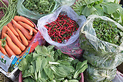 Carrots, red chillies, green leafy vegetables and herbs for sale at Daeum Kor morning market in Phnom Penh, the capital city of Cambodia. A large variety of local products are available for sale in fresh markets all over Cambodia, all being sold on small individual stalls.
