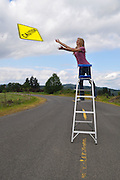 """Humorous photograph of a woman throwing a CAUTION warning sign into the air visually depicting the saying """"Throw caution to the wind""""."""