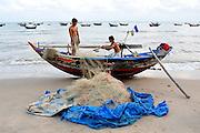 Fishermen stowing net and lines aboard their boat. Mui Ne, Vietnam