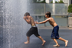 © Licensed to London News Pictures. 11/07/2013. London, UK. Boys cool off from the summer heat in Danish artist Jeppe Hein's interactive fountain outside the Queen Elizabeth Hall on London's South Bank today (11/07/2013). Photo credit: Matt Cetti-Roberts/LNP