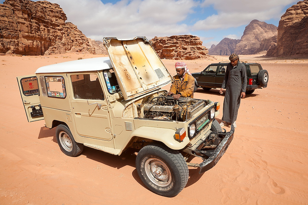 Bedouin guides service a broken down jeep in the desert in Wadi Rum, Jordan.