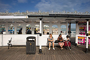 Women relaxing in the afternoon sun at Brighton Pier on the 19th July 2018 in Brighton in the United Kingdom. The Brighton Palace Pier, commonly known as Brighton Pier or the Palace Pier is a Grade II* listed pleasure pier in Brighton, England, located in the city centre opposite the Old Steine.