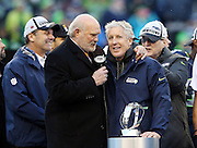 (L-R) Sports analyst and former Pittsburgh Steelers quarterback Terry Bradshaw congratulates Seattle Seahawks head coach Pete Carroll after the Seahawks win the NFL week 20 NFC Championship football game against the Green Bay Packers on Sunday, Jan. 18, 2015 in Seattle. The Seahawks won the game 28-22 in overtime. ©Paul Anthony Spinelli