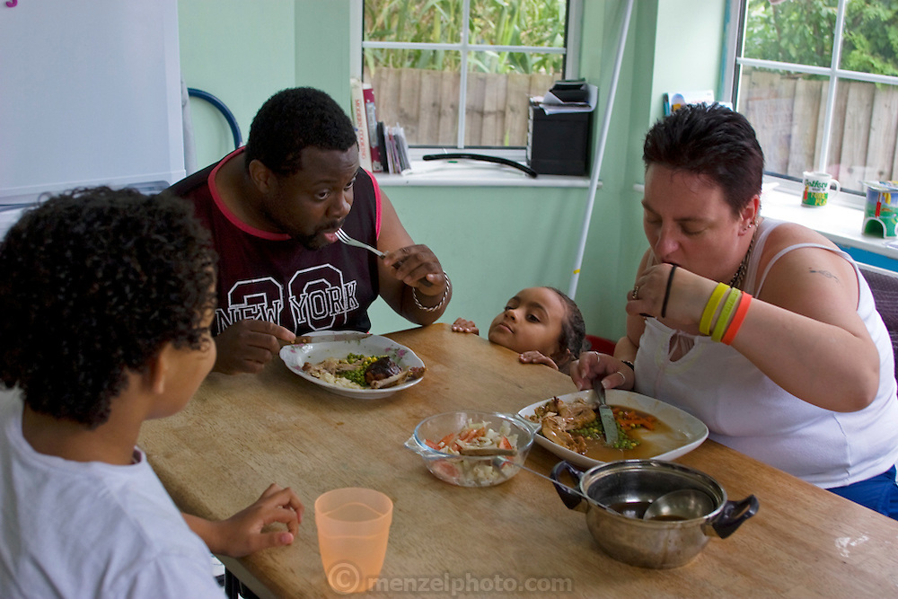 "Jill McTighe, a mother and school aide,  enjoys dinner with her husband Earl Gillespie and their children at their home in Willesden, London, United Kingdom. (From the book What I Eat: Around the World in 80 Diets.) The caloric value of her day's worth of food on a ""bingeing"" day in the month of September was 12300 kcals. The calorie total is not a daily caloric average.  Jill is 31 years old; 5 feet, 5 inches tall;  and 230 pounds. Honest about her food addiction replacing a drug habit, Jill joked about being a chocoholic as she enthusiastically downed a piece of chocolate cake at the end of the photo session. Her weight has yo-yoed over the years and at the time of the picture she was near her heaviest; walking her children to school every day was the sole reason she didn't weigh more. She says this photo experience was a catalyst for beginning a healthier diet for herself and her family. ""Do I cook? Yes, but not cakes. I roast. Nothing ever, ever is fat-fried!"" Jill herself is MODEL RELEASED.  [Use of Jill McTighe images must be used contextually only and use cleared with Peter Menzel Photography on a case by case basis.]"