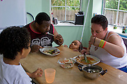 """Jill McTighe, a mother and school aide,  enjoys dinner with her husband Earl Gillespie and their children at their home in Willesden, London, United Kingdom. (From the book What I Eat: Around the World in 80 Diets.) The caloric value of her day's worth of food on a """"bingeing"""" day in the month of September was 12300 kcals. The calorie total is not a daily caloric average.  Jill is 31 years old; 5 feet, 5 inches tall;  and 230 pounds. Honest about her food addiction replacing a drug habit, Jill joked about being a chocoholic as she enthusiastically downed a piece of chocolate cake at the end of the photo session. Her weight has yo-yoed over the years and at the time of the picture she was near her heaviest; walking her children to school every day was the sole reason she didn't weigh more. She says this photo experience was a catalyst for beginning a healthier diet for herself and her family. """"Do I cook? Yes, but not cakes. I roast. Nothing ever, ever is fat-fried!"""" Jill herself is MODEL RELEASED.  [Use of Jill McTighe images must be used contextually only and use cleared with Peter Menzel Photography on a case by case basis.]"""